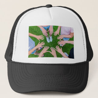 Many children hands joining in circle above grass trucker hat