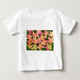 Many colorful autumn maple leaves on green grass baby T-Shirt
