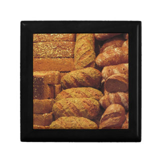 Many mixed breads and rolls background small square gift box