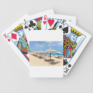Many reed beach umbrellas in a row  on empty beach bicycle playing cards