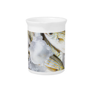 Many small caught dead fish with ice on market drink pitchers