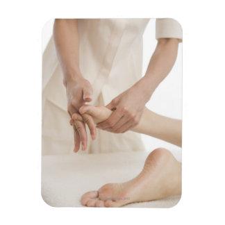 Massage therapist applying foot massage 2 rectangular photo magnet