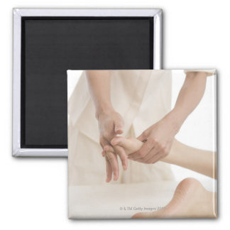 Massage therapist applying foot massage 2 square magnet