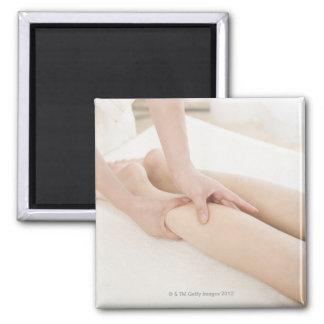 Massage therapist applying foot massage square magnet