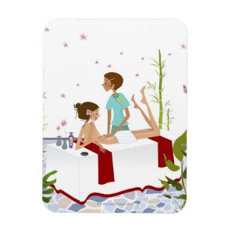 Massage therapist massaging a woman lying on a rectangular photo magnet