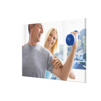 Mature woman smiling at mature man lifting gallery wrapped canvas