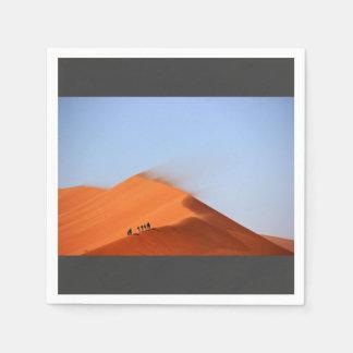 Men standing on sand dune in desert paper napkin