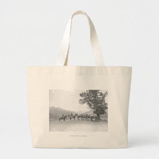 Men with packhorses looking over a hill large tote bag