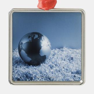 Metal globe on shredded paper metal ornament