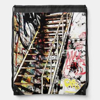 metal urban staircase with graffiti drawstring bag
