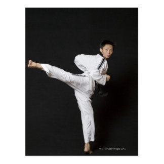 Mid adult man performing the side kick postcard