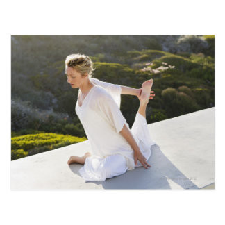 Mid adult woman practicing yoga exercise at postcard