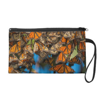 Migrating monarch butterflies cling to leaves wristlet clutch