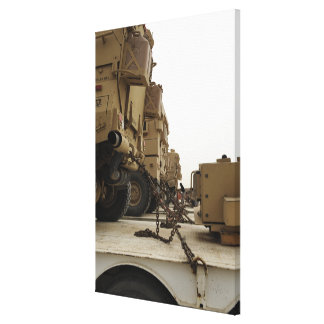 Military vehicles are locked down on semi truck canvas print