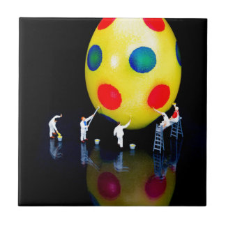 Miniature figurines painting yellow easter egg ceramic tile