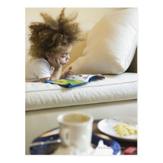 Mixed race boy reading book on sofa postcard