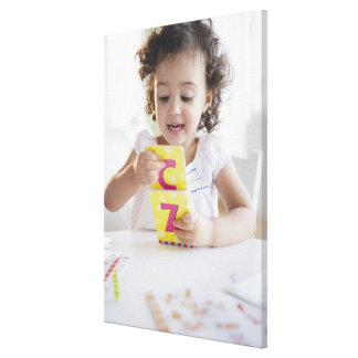 Mixed race girl playing with alphabet cards canvas print