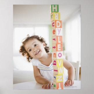 Mixed race girl stacking blocks poster