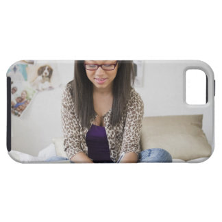 Mixed race teenage girl doing homework on bed case for the iPhone 5