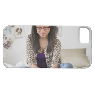Mixed race teenage girl doing homework on bed iPhone 5 cases