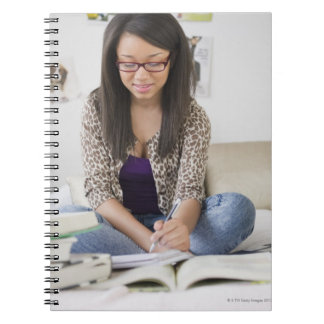 Mixed race teenage girl doing homework on bed note book