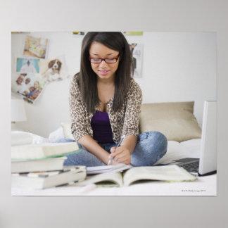Mixed race teenage girl doing homework on bed poster