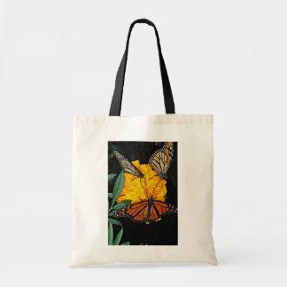 Monarch butterflies feeding  flowers tote bags