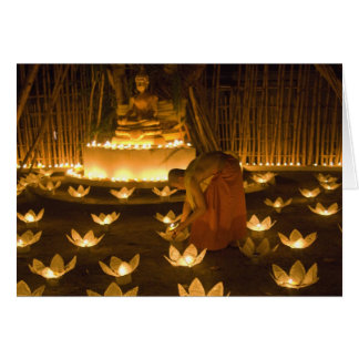 Monks lighting khom loy candles and lanterns for greeting card