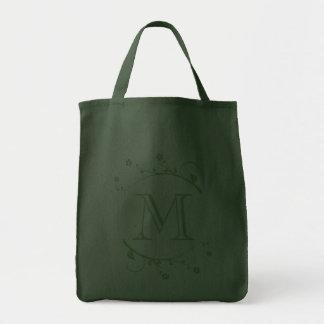 Monograma verde y ramas en flor en bolsa