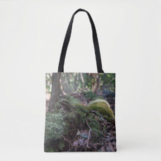 Moss covered fallen tree in a forest tote bag