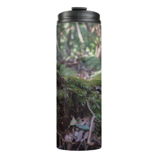 Moss covered fallen tree in forest thermal tumbler