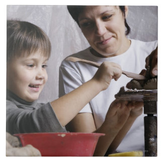 mother and daughter forming sculpture out of large square tile