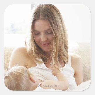 Mother breastfeeding her child square sticker