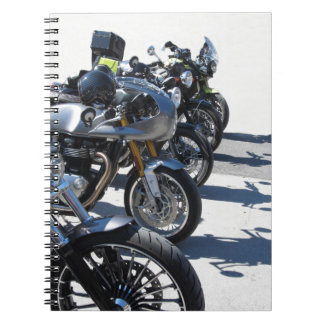 Motorcycles parked in row on asphalt notebooks
