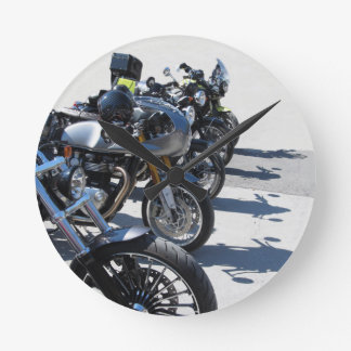 Motorcycles parked in row on asphalt round clock