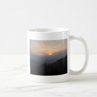 mountain sunset in a haze coffee mug