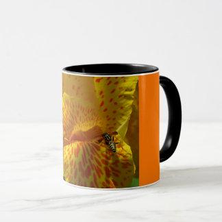 Mug close-up of yellow orange flower with hornet