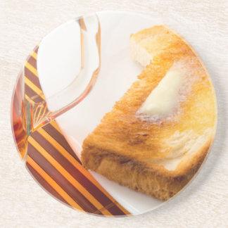 Mug of tea and hot toast with butter coaster