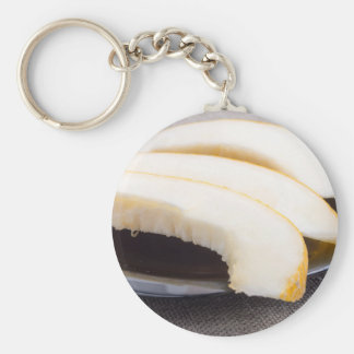 Natural pieces of yellow melon on a black plate key ring