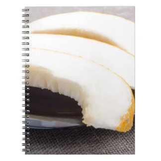 Natural pieces of yellow melon on a black plate note books