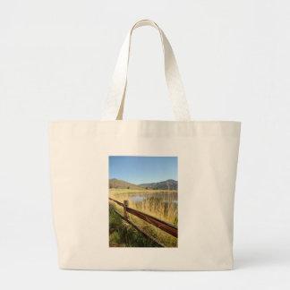 Nevada landscape with wood fence, lake, sky. large tote bag