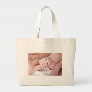 newborn baby holding fathers finger tote bag