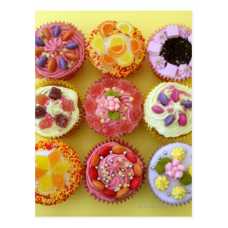 Nine cupcakes each decorated with candy in a postcard