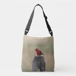 Northern cardinal stands on a fence post crossbody bag