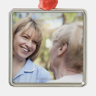 Nurse smiling and talking to a senior woman ornaments