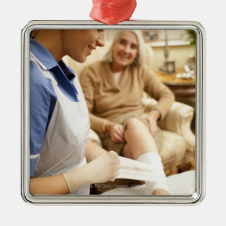Nurse wrapping bandage on senior woman's leg to Silver-Colored square decoration