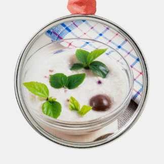 Oatmeal in a bowl of glass with chocolate candy metal ornament