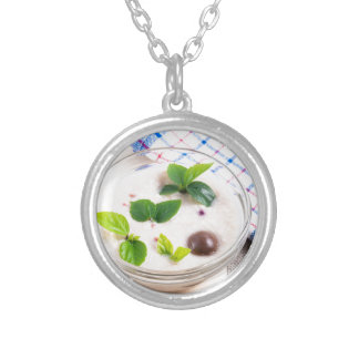 Oatmeal in a bowl of glass with chocolate candy silver plated necklace