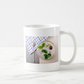 Oatmeal with chocolate candy and a silver spoon coffee mug