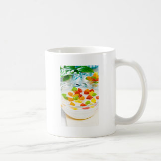 Oatmeal with colorful candied fruits in a glass coffee mug